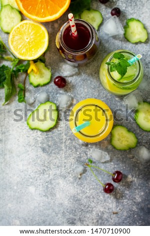 Various refreshments drinks - detox cucumber water, cherry juice and orange juice on stone table. Top view flat lay. #1470710900