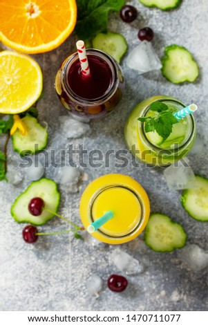 Various refreshments drinks - detox cucumber water, cherry juice and orange juice on stone table. Top view flat lay. #1470711077