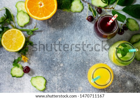 Various refreshments drinks - detox cucumber water, cherry juice and orange juice on stone table. Top view flat lay with copy space for your text. #1470711167