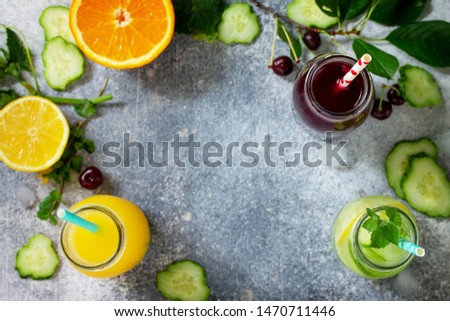 Various refreshments drinks - detox cucumber water, cherry juice and orange juice on stone table. Top view flat lay with copy space for your text. #1470711446