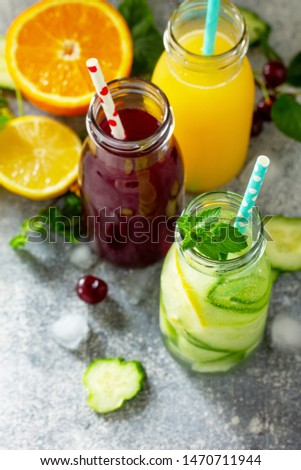 Various refreshments drinks - detox cucumber water, cherry juice and orange juice on stone table. Copy space for your text. #1470711944