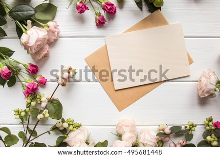 Various roses on white rustic wooden background with empty card for greeting message. Mother's Day and spring background concept. Holiday mock up. Top view. #495681448