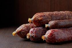 various salami sausages on dark brown table