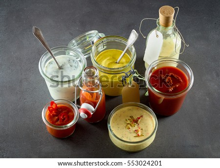 Shutterstock Various sandwich condiments in different sized glass containers and jars bunched together over gray background
