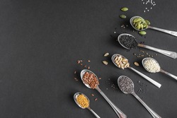 Various Seeds Assortment on black background. Set of  sesame seeds, flax seed, sunflower seeds, pumpkin seed, chia, hemp seeds in spoons, healthy food ingredients, top view, copy space.