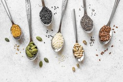 Various Seeds Assortment on white background. Set of  sesame seeds, flax seed, sunflower seeds, pumpkin seed, chia, hemp seeds in spoons, healthy food ingredients, top view, copy space.
