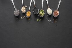 Various Seeds on black background. Assortment, set of  sesame seeds, flax seed, sunflower seeds, pumpkin seed, chia, hemp seeds in spoons, healthy food ingredients, top view, copy space.