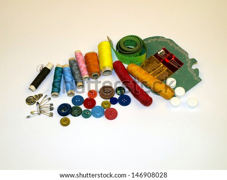 various sewing accessories, against a solid background