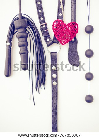 Various sex toys (dildo, whip, harness, anal balls and others) hang on a light background. Together with them hangs a red wicker heart. Image for advertising sex products store on St. Valentine's Day #767853907