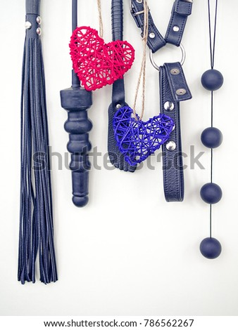 Various sex toys (dildo, whip, harness, anal balls) hang on a light background. Together with them hangs a red and blue wicker hearts. Image for advertising sex products store on St. Valentine's Day #786562267