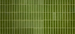 Various shades of glazed green mosaic ceramic tiles on wall textured background