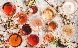 Various shades of rose wine. Flat-lay of rose wine in different colors in glasses and spring blossom flowers over marble background, top view. Wine shop, bar, tasting, seasonal wine list concept
