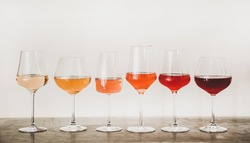 Various shades of Rose wine in stemmed glasses placed in line from light to dark colour on concrete table, white wall background behind. Wine bar, wine shop, wine tasting concept