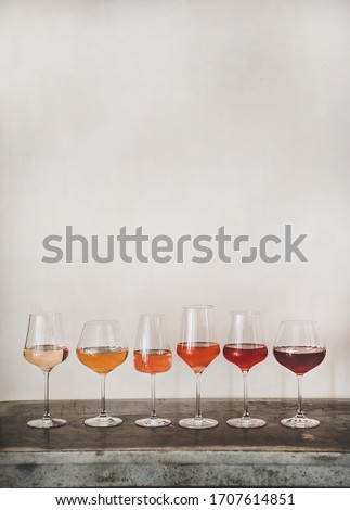 Various shades of Rose wine in stemmed glasses placed in line from light to dark colour, white wall background behind, copy space. Wine bar, wine shop, wine tasting concept