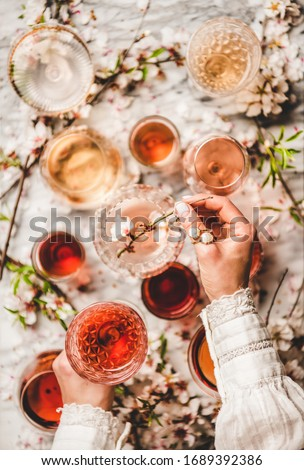 Various shades of rose wine. Womans hands over rose wine of different colors in glasses and spring blossom flowers over white background, top view. Wine shop, bar, wine tasting concept