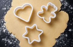 Various shaped cookie cutter on dough preparing cookies concept