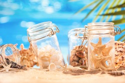 Various shells and starfish in jars on the azure seashore. Vacation shells. Nostalgia for a tropical getaway. Summer sunny background.