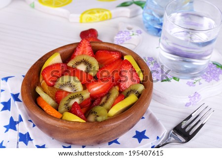 Various sliced fruits in bowl on table close-up