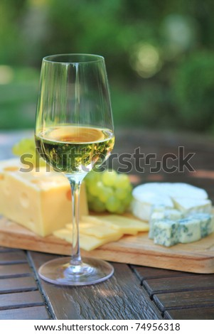 Various sorts of cheese, grapes and one glass of the white wine