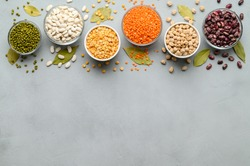 Various sources of vegetable protein: beans, lentils, peas, chickpeas, mung bean in bowls. A healthy balanced diet for vegans and vegetarians. Gray stone background. Top view, copy space.