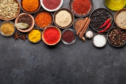 Various spices in bowls on dark stone table. Indian cuisine. Top view flat lay with copy space