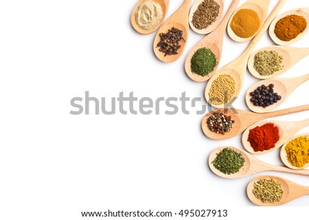 Various spices in wooden spoons isolated on white background.