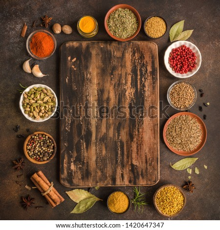 Various Spices on dark wooden background. Assortment, set of spices and condiments with cutting board, top view, copy space. Cooking food concept.
