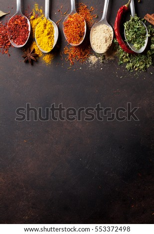 Various spices spoons on stone table. Top view with copy space