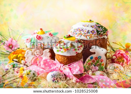 Various Spring Easter cakes with white icing and sugar decor on the table decorated in rustic style