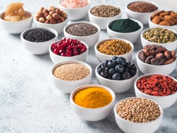 Various superfoods in smal bowl gray concrete background. Superfood as chia, spirulina, raw cocoa bean, goji, hemp, quinoa, bee pollen, black sesame, turmeric. Copy space for text.