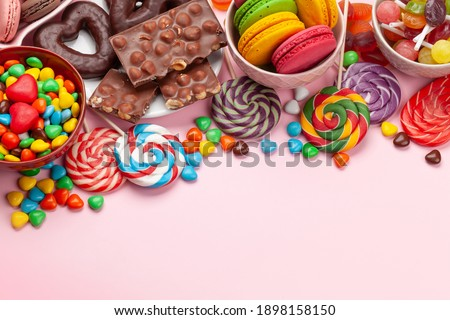Various sweets assortment. Candy, bonbon and macaroons on pink background. Top view with copy space Stock foto ©