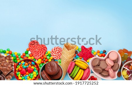 Various sweets assortment. Candy, bonbon, chocolate and macaroons over blue background. Top view flat lay with copy space ストックフォト ©