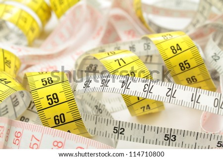 Various tape measure as background.