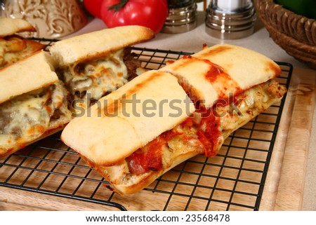 Various toasted submarine sandwiches with chicken, beef, melted cheese, vegetables, and marinara sauce.
