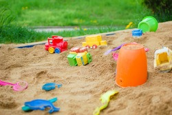 Various toys scattered in a sandpit.