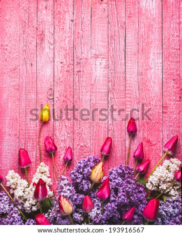 Various tulips and lilac on pink wooden background