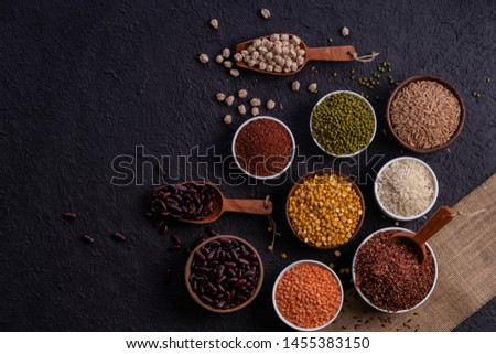 Photo of  Various type of cereal grains, rice,brown rice, buckwheat, barley, ,millet. Various raw uncooked grains on dark background pulses, grains, seeds and millet.