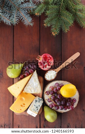 Various type of cheese and fruits on wooden boards and Christmas tree twigs. Swiss cheese, blue cheese, camembert and cottage cheese for Christmas. Dairy products, lemon, grapes and pears. Top view