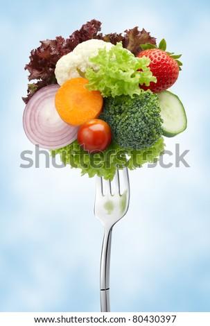 various type of vegetables on fork against blue background
