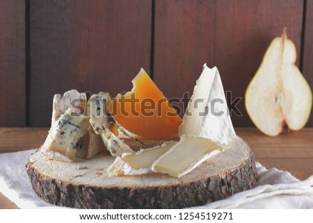 Various types of cheese and pieces of pear on wooden boards. Blue cheese, camembert and hard cheese on wooden stand. Dairy product on white napkin. Assortment of cheese and ripe pear