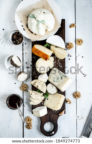 Various types of cheese. On a white wooden background. Blue cheeses with spices. Around honey and walnuts. Home cheese dairy.