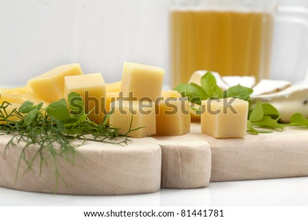 Various types of cheese on a wooden board with beer