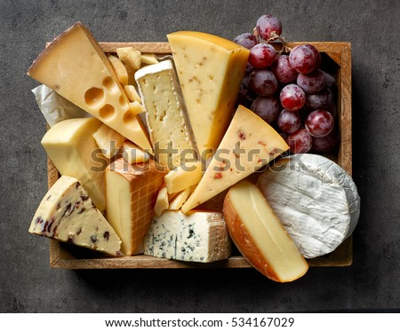various types of cheese on dark gray kitchen table, top view