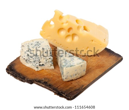 Various types of cheese on old wooden kitchen board. Isolated on white background.