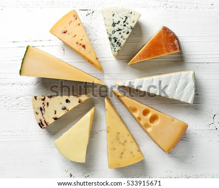 various types of cheese on white wooden table, top view