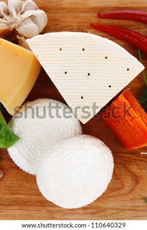 various types of cheese on wooden board with hot peppers and dill isolated over white background