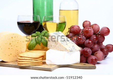 Various types of cheese (swiss, yellow, brie, blue cheese) with red and white wine, red grapes and crackers on white background in close up