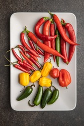 Various types of chili peppers. Chili, habanero and jalapeno peppers. Red, green and yellow hot peppers on plate. Top view.
