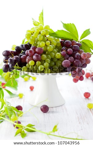 Various types of grapes with leaves on a cake stand