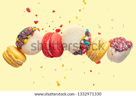 Various types of macaroon macaroons in motion, falling on a yellow background. Colorful and sweet French macaroons fall or fly in motion, with particles and crumbs.